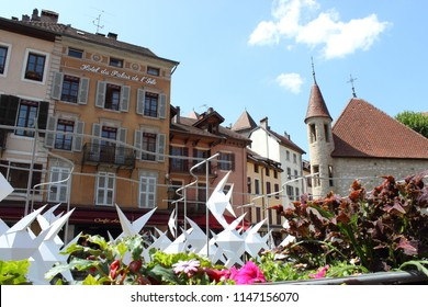 ANNECY, HAUTE SAVOIE / FRANCE JULY 22 2018: original view of the palace of the island, the palace hotel and the old facades, which seem to stifle the work of the artist Antoine Milian, the flying fish