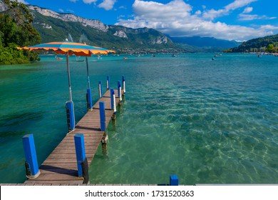 Annecy, Haute-Savoie, Auvergne-Rhône-Alpes / France - September 13, 2014: A jetty and pedal boats on Lake Annecy, one of the largest and cleanest lakes in France, viewed from Jardins de l'Europe park.