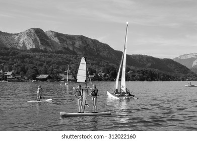 ANNECY LAKE, FRANCE - AUGUST 27, 2015: Tourists enjoy from water sports (sailing, kayaking) at Annecy lake surrounded by beautiful mountains. Annecy Lake is one of the most popular French resorts.