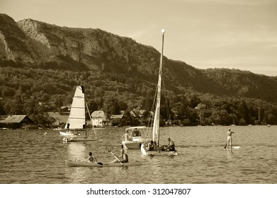 ANNECY LAKE, FRANCE - AUGUST 27, 2015: Tourists enjoy water sports (sailing, kayaking) at Annecy lake surrounded by beautiful mountains. Annecy Lake is one of the most popular French resorts.