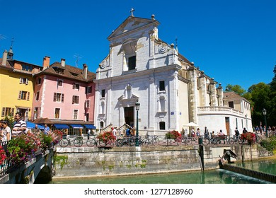 Annecy,France-08 23 2016:Cityscape of Annecy with the white facade of the Saint François's church, nearby the Thiou river.