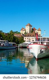 Annecy,France-08 23 2016:The Annecy Castle which was the home of the Counts of Geneva, dominates the old French town of Annecy,and tour boats moored on the lake, ready for summer touristic season.