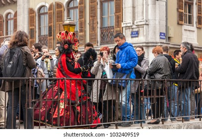 Annecy,France-March 15,2014: A disguised person is surrounded by a crowd of tourists and photographers on the Perrier Bridge during the Annecy Venetian Carnival.