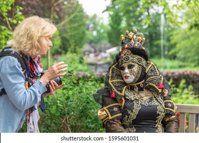 ANNEVOIE GARDENS, BELGIUM - June 9, 2019: A famail photographer talking with a woman in a carnival venitian costume in Annevoie gardens, Belgium.