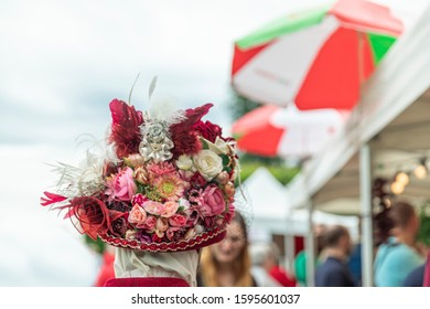 ANNEVOIE GARDENS, BELGIUM - June 9, 2019: Woman in a carnival hat from the back in Venice costume in Annevoie gardens, Belgium.