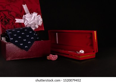 Anniversary gift concept. Beautiful silver pearl necklace in red box, candy wih blue tie and decorative gift box on black background