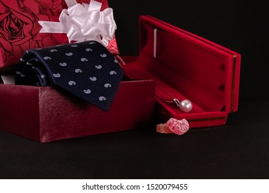 Anniversary gift concept. Delicate Pearl Shaped Pendant Necklace in red box, decorated gift box with a blue tie and candy in black background