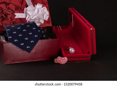 Anniversary gift concept. Silver pearl necklace in red box, candy wih blue tie and decorated gift box on black background