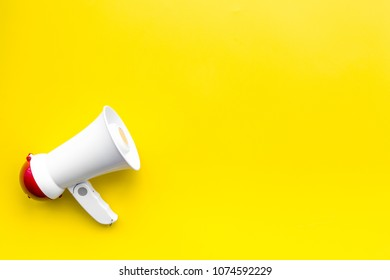 Announcement concept. Megaphone on yellow background top view copy space