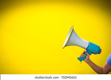 announcement concept,woman hand is holding megaphone on yellow background,copy spcae