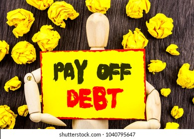 Announcement text showing Pay Off Debt. Concept meaning Reminder To Paying Owed Financial Credit Loan Bills written Sticky Note Holding By Sculpture the wooden background