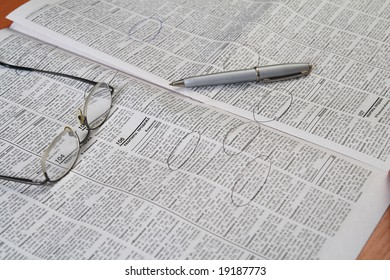 announces in newspaper with glasses and pen