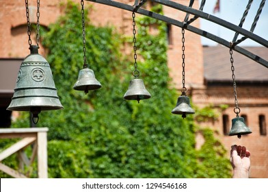 Announcing a daily prayer. Metal bells on metallic chains hung on arc in church yard. Church bells hanging outdoor. Bells ringing on wind. Calling to christian mass or service of worship.