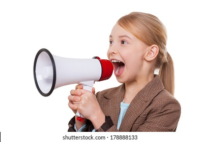 Announcing good news. Cheerful little girl in formalwear shouting at megaphone while standing isolated on white
