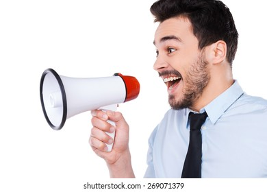 Announcing good news. Side view of happy young man in shirt and tie holding megaphone and shouting while standing against white background