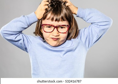 annoyed 6-year old little child with eyeglasses scratching her head for small tantrum or pulling out her hair for itchy lice or allergies, grey background