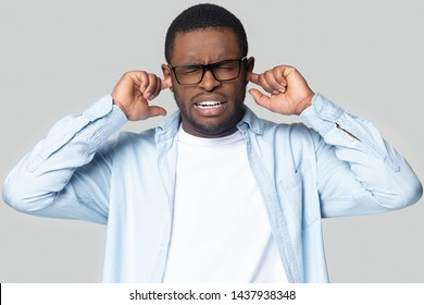 Annoyed african American millennial man in glasses close plug ears avoid unpleasant disturbing sound, unhappy black male in spectacles isolated on grey studio background bothered by bad loud noise