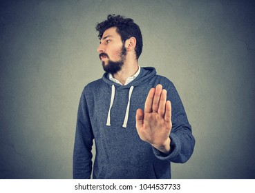 Annoyed angry man with bad attitude giving talk to hand gesture isolated on gray background. Negative emotion face expression feeling body language