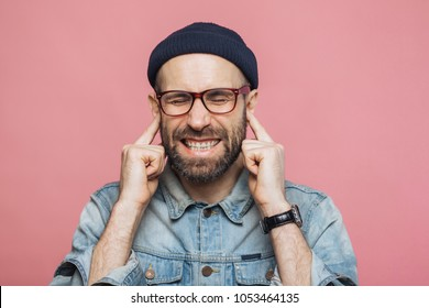 Annoyed bearded male plugs ears as hears unpleasant sound, keeps eyes shut, being dissatisfied with something, isolated over pink background. Unshaven middle aged male ignores hearing someone