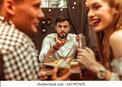 Annoyed bored man. Handsome short-haired nice-appealing young-adult annoyed bored man holding a burger and feeling lonely while his friends are flirting with each other