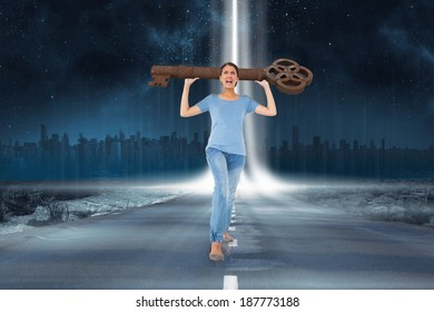 Annoyed brunette carrying large key against road leading out to the horizon with light beam
