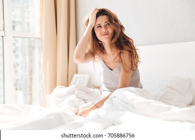 Annoyed brunette woman sitting in pajamas in bed and looking up at home