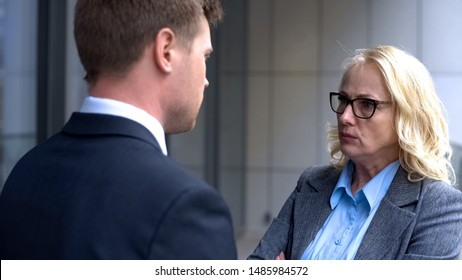 Annoyed business woman looking male company worker, corporate subordination