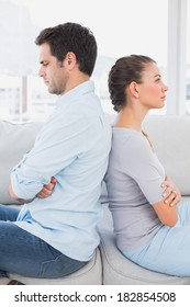 Annoyed couple sitting back to back on the couch at home in the living room