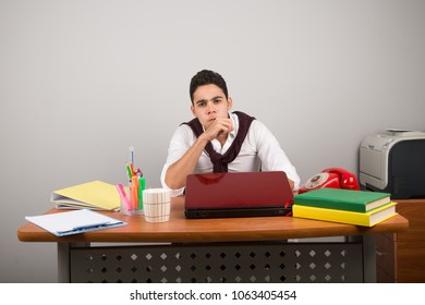 Annoyed employee sitting on his desk blowing exasperated.