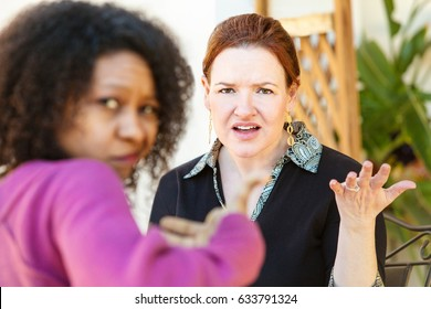 Annoyed European woman sitting with friend and gesturing with hand