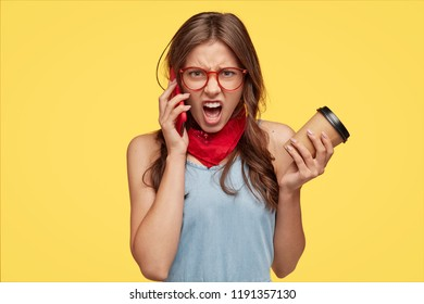 Annoyed European woman yells with negative feelings while has telephone conversation, argues with boyfriend on distance, carries coffee in disposable cup, isolated over yellow studio background
