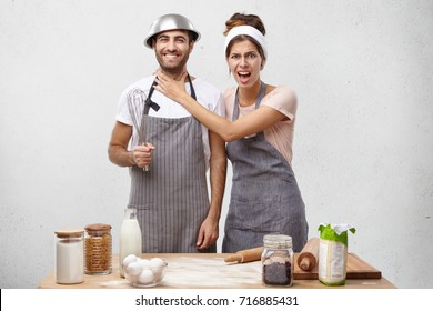 Annoyed female keeps hand on husband`s neck, asks to help with cooking tasty dinner. Pretty woman wears apron and bearded smiling young guy foolish together at kitchen, pretend professional cookers