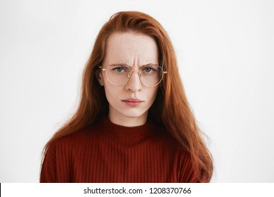 Annoyed female student with freckles and ginger hair posing isolated at studio wall, having displeased offended facial expression, pouting lips and frowning, dissatisfied with resluts of examination