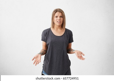 Annoyed frowning woman with short dyed hair wearing loose grey T-shirt gesturing with her hands having tattoos on them having uncertainty and confusion. Angry female posing against white wall