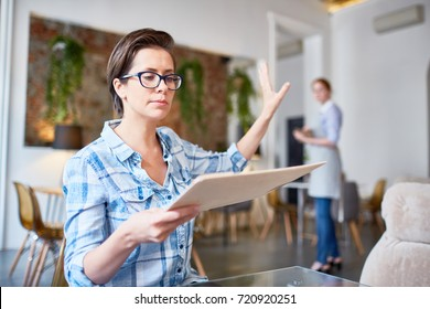 Annoyed guest of cafe or restaurant reading menu and asking waitress to bring her book of feedbacks