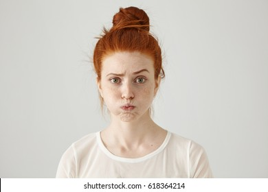 Annoyed irritated young red-haired female with freckles blowing her cheeks, frowning, feeling frustrated with something. Human facial expressions, emotions and feelings. Fatigue or boredom concept