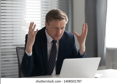 Annoyed mad businessman wearing suit frustrated with online problem, angry stressed male professional using laptop outraged by broken pc, crazy about stuck slow computer virus app error at workplace