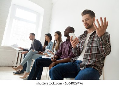 Annoyed man frustrated with phone problem, angry businessman confused by not working mobile, no internet connection, mad about missed call, bad signal, low battery sitting in row with diverse people