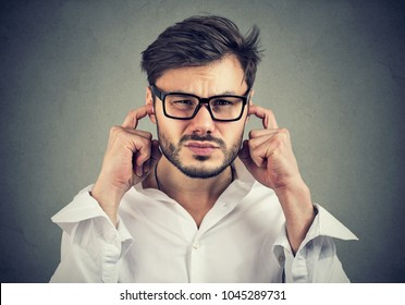 Annoyed man looking grumpy plugging with fingers ears unwilling to listen to anyone.