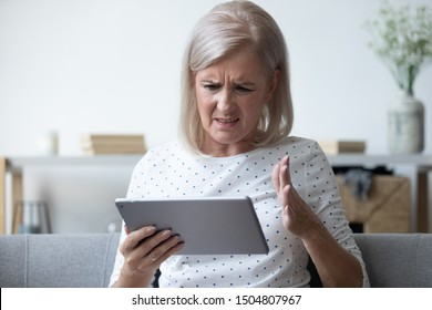 Annoyed mature woman having problem with broken or discharged computer tablet, angry older female irritated by spam message or bad news, looking at electronic device screen close up