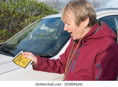Annoyed mature woman holding a parking ticket