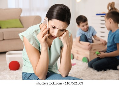 Annoyed nanny talking on phone while two little boys are playing at home