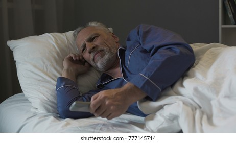Annoyed pensioner suffering insomnia and nervously switching TV channels