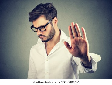 Annoyed sad man giving talk to hand gesture isolated on gray background. Negative emotion face expression feeling body language