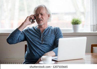 Annoyed senior man argue over phone explaining his point of view to another person, serious aged male bothered by unpleasant cellphone talk, modern elderly using laptop have discussion over smartphone
