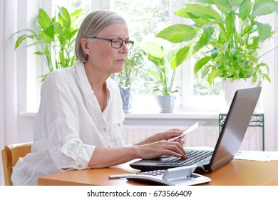 Annoyed senior woman at home with a calculator and lots of receipts in front of her laptop making her annual tax declaration