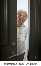 Annoyed senior woman opening front door