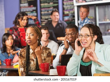 Annoyed students watching loud woman on cell phone