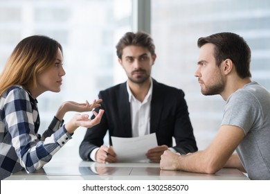 Annoyed unhappy married couple arguing in lawyers office get divorced, angry family spouses split up having disagreement disputing about breaking up and divorce settlement, legal separation concept