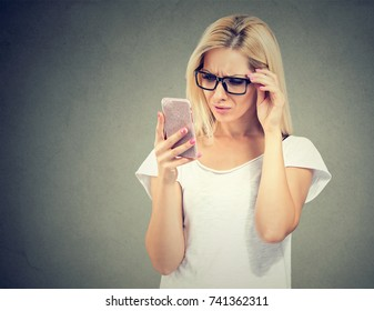 Annoyed upset woman in glasses looking at her smart phone with frustration